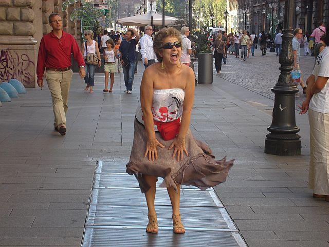 Segurando a saia para o vento não levantar em Milão na Itália