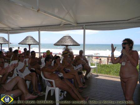 Em um dia lindo de sol na praia o povo ali assistindo palestra