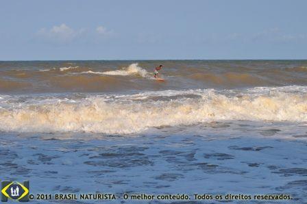 Ele é um ponto deslizando de prancha na imensidão do mar