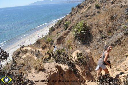 Daniela escalando a trilha que leva a praia lá embaixo