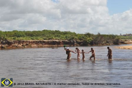 Fazendo a travessia do rio Ipiranga/Barra Seca/ES com os pertences na mão enrolado na canga