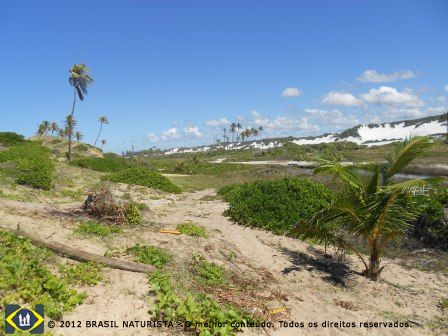 As dunas de areia brancas cercam a praia entre o rio e o mar