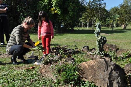 A filha e a sobrinha da Cris no momento da colocação das cinzas na raiz do girassol...